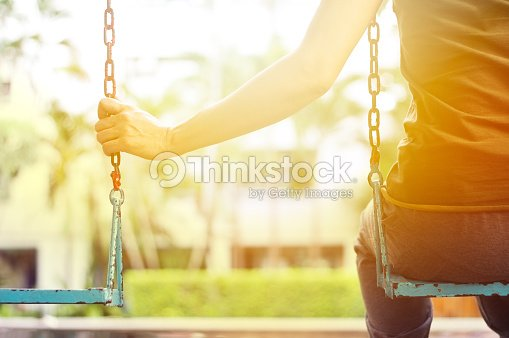 Lonely woman missing her boyfriend while swinging in the park : Stock Photo