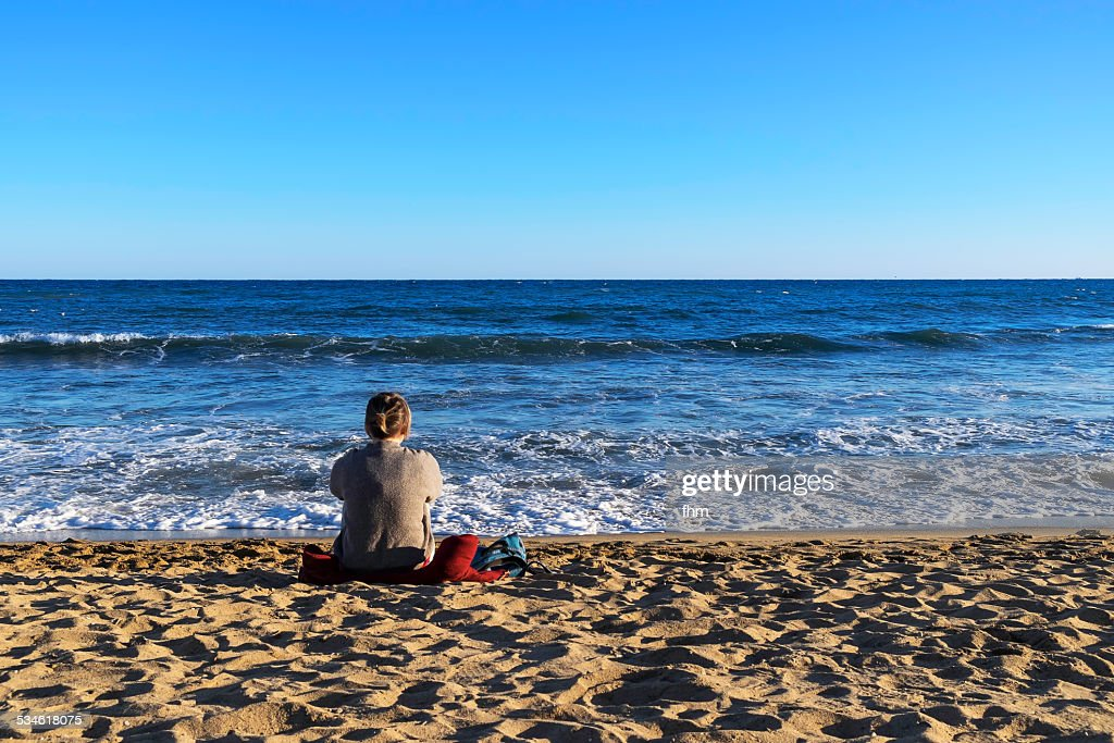 Lonely woman sitting at the beach