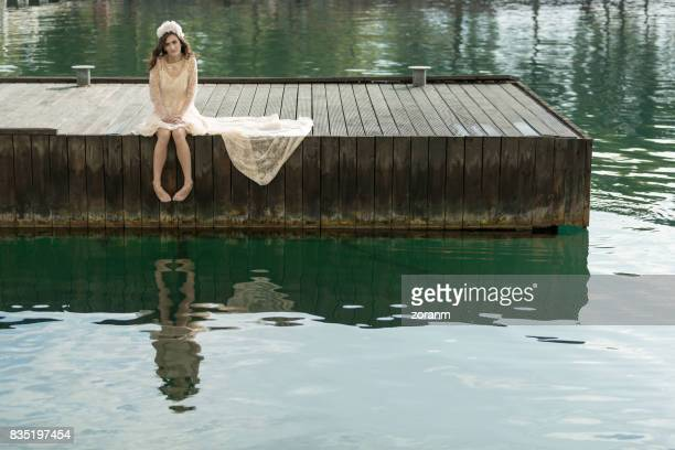 Lonely woman sitting on a jetty