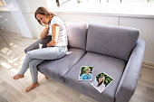Lonely Woman Sitting On Sofa With Torn Photograph