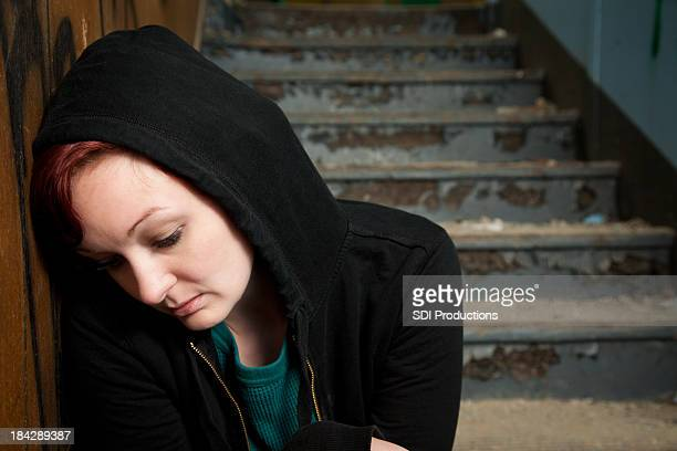 Lonely Woman Sitting on Stairs In Run-Down Building