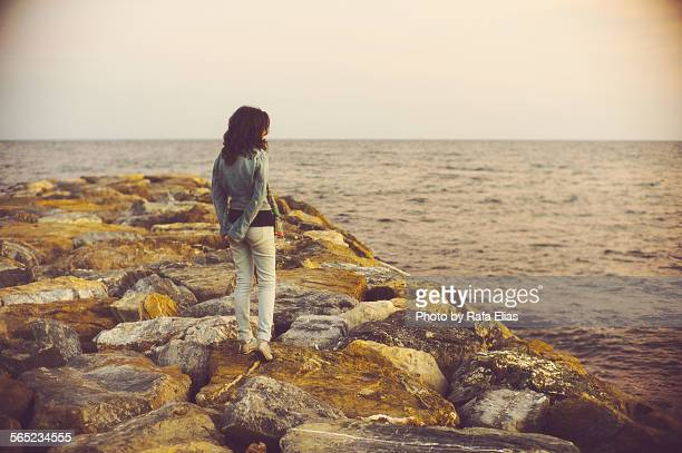 Lonely woman standing on stone dock