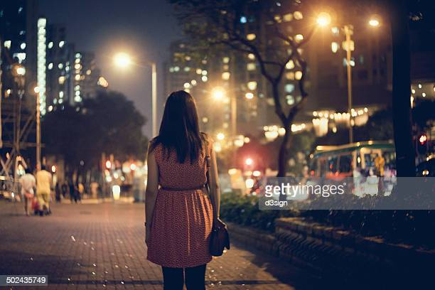 Lonely  woman walking along the city street