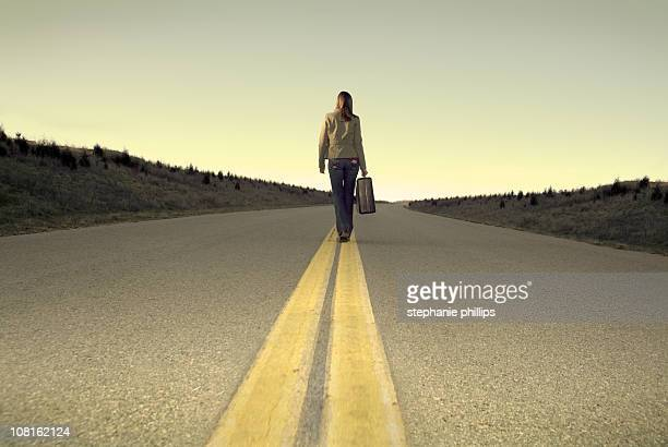 Lonely Woman Walking down the Road with Her Luggage