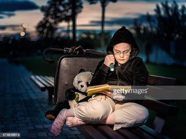 Solitario giovane ragazza seduta su una panca