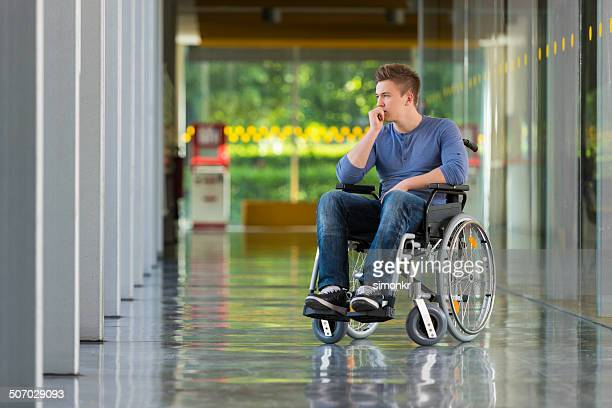 Einsame junge Mann im Rollstuhl