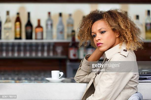 Lonely young woman drinking coffee in a bar