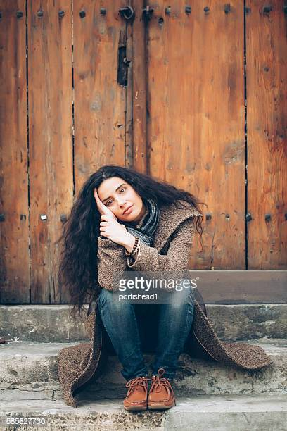 Lonely young woman sitting in front of a closed door