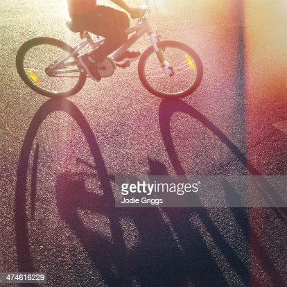 Long afternoon shadow of child riding bicycle