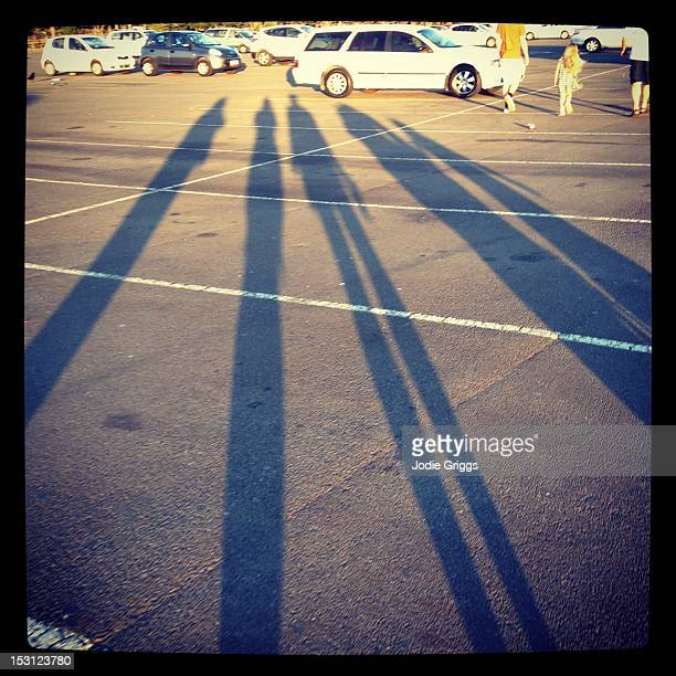 Long afternoon shadows of five people walking