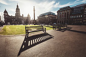 Long benches shadows on the George Square - the principal civic square in the city of Glasgow, Scotland.