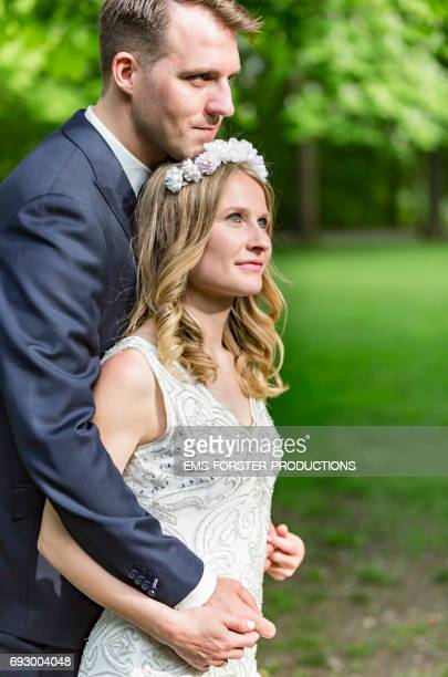 long blonde haired bride wearing floral headband and her white wedding dress gets hugged from behind of her tall brown haired groom who wears his wedding suit outside in a green park