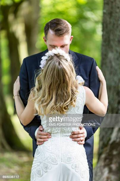 long blonde haired bride wearing floral headband and her white wedding dress gets hugged and kissed by her tall brown haired groom in his wedding suit outside in a green park on a sunny day after the wedding ceremony
