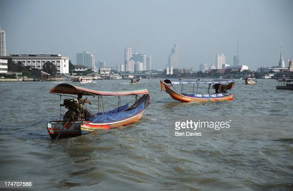 Long boats sail along Bangkok's Chao Phraya River known as the river of kings which cuts through the heart of the capital city The river passes such...