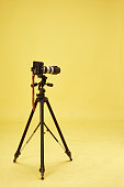 modern professional camera on tripod on white background