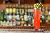 Long Drink fruit sling is on a bar counter on a blurry background of bottles with alcohol in a nightclub. Space for text design or a recipe in the menu