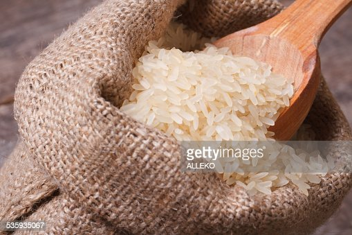 long dry rice on wooden spoon macro in the sack : Stock Photo
