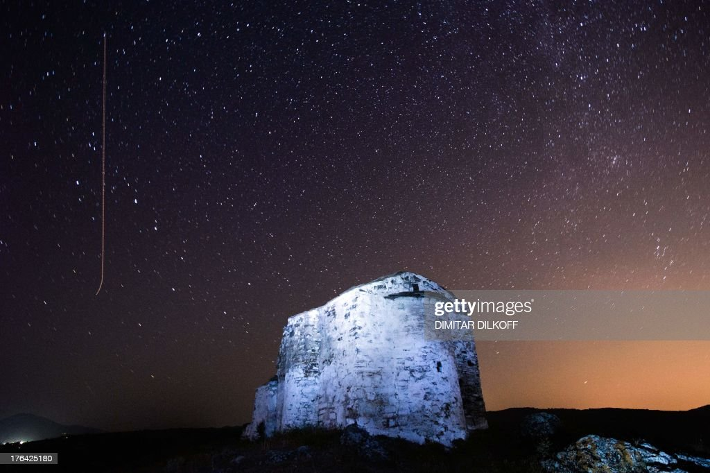 A long exposure image showing a Perseids meteor (L) streaking across the night sky over St. Ioan medieval church near the village of Potsurnentsi, late on August 12, 2013. The Perseid meteor shower occurs every year in August when the Earth passes through the debris and dust of the Swift-Tuttle comet. AFP PHOTO / Dimitar DILKOFF