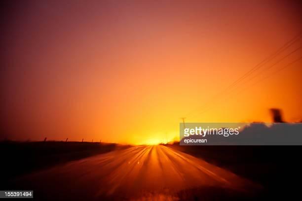 Langzeitbelichtung Sie einen brillianten Sonnenuntergang spiegelt auf die country road