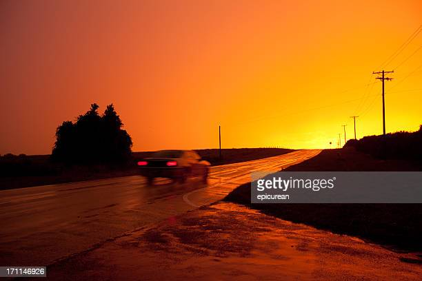 Long exposure of a brilliant sunset reflecting on country road