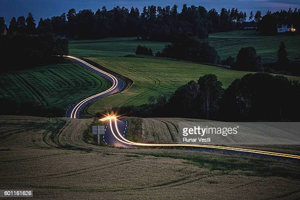 Long exposure of car driving on a curvy road in the countryside.