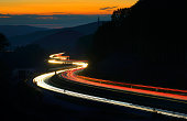 Winding Motorway through Hills, long exposure of Car Lights at Dusk