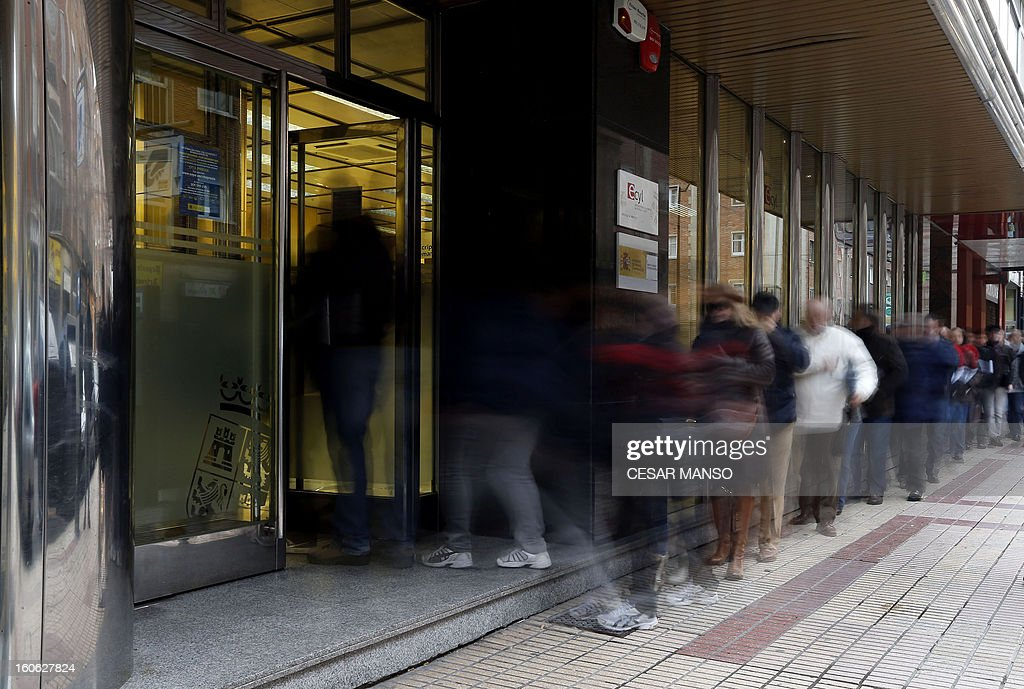 A long exposure photo shows people waiting outside a government employment office in Burgos on February 4, 2013.The number of Spaniards officially registered as unemployed rose to 4.98 million in January, according to Labour Ministry data released today, as the country's recession deepened.
