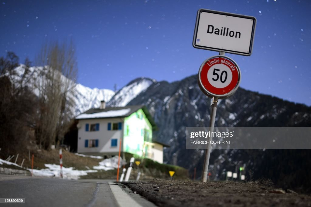 A long exposure photograph shows a sign reading 'Daillon' on the side of a road leading into the village of Daillon after it was closed to the press early on January 3, 2013. A gunman has opened fire in a village in southern Switzerland, killing three people and wounding two others, police said on January 3.