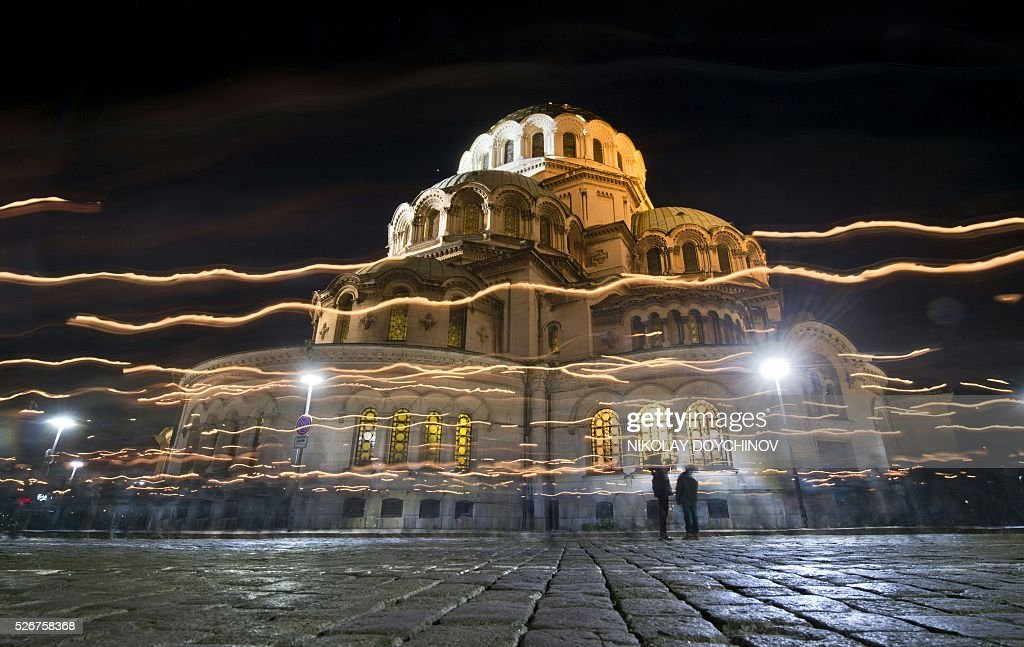 A long exposure picture shows Bulgarians walking with candles outside the golden-domed Alexander Nevski Cathedral after an Easter service in Sofia early on May 1, 2016. Orthodox Christians are celebrating Easter Sunday on May 1. / AFP / NIKOLAY