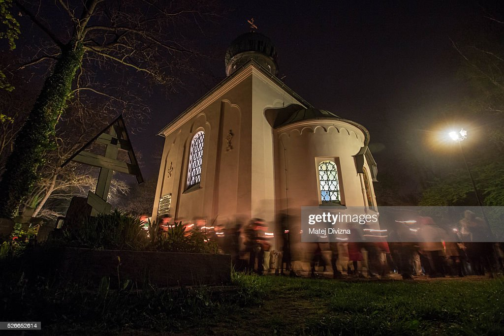 Long exposure shows worshippers walking around the Orthodox Church of the Dormition during the Orthodox Easter ceremony at the Olsany Cemetery on May 1, 2016 in Prague, Czech Republic. The Greek Orthodox world celebrates Easter Day according to the old Julian calendar.