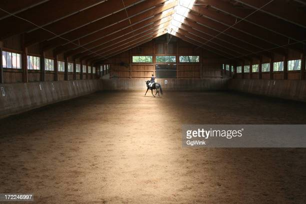 Long farm cabin with a man riding a horse