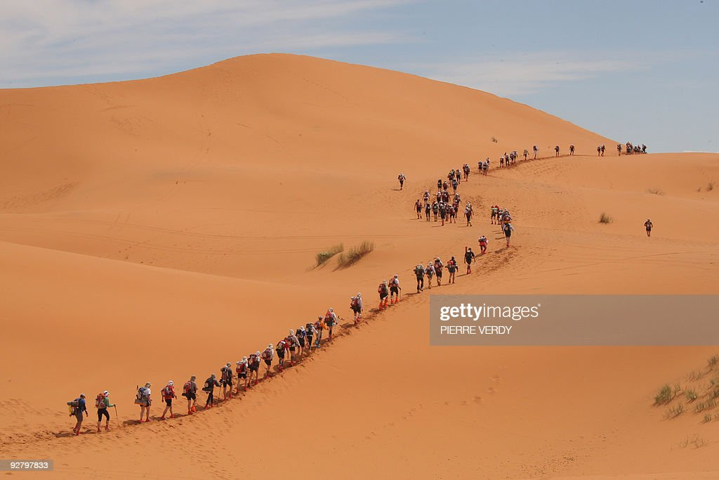 A long file of competitors take the start of the 24th Marathon des Sables in the Sahara desert on March 30 2009 climbing the first dunes of Merzouga...