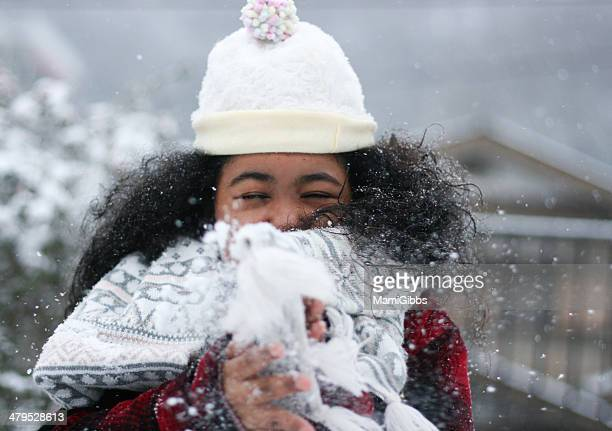 Long hair girl is playing with the snow