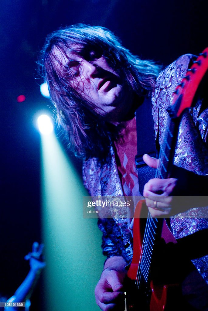 Long Haired Man Playing Guitar on Stage : Stock Photo