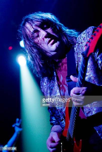 Long Haired Man Playing Guitar on Stage