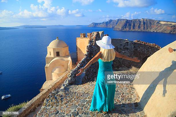 Long haired woman with beach hat in Oia, Santorini