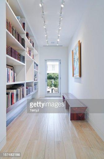 Lungo corridoio con libreria integrata che portano all'aperto