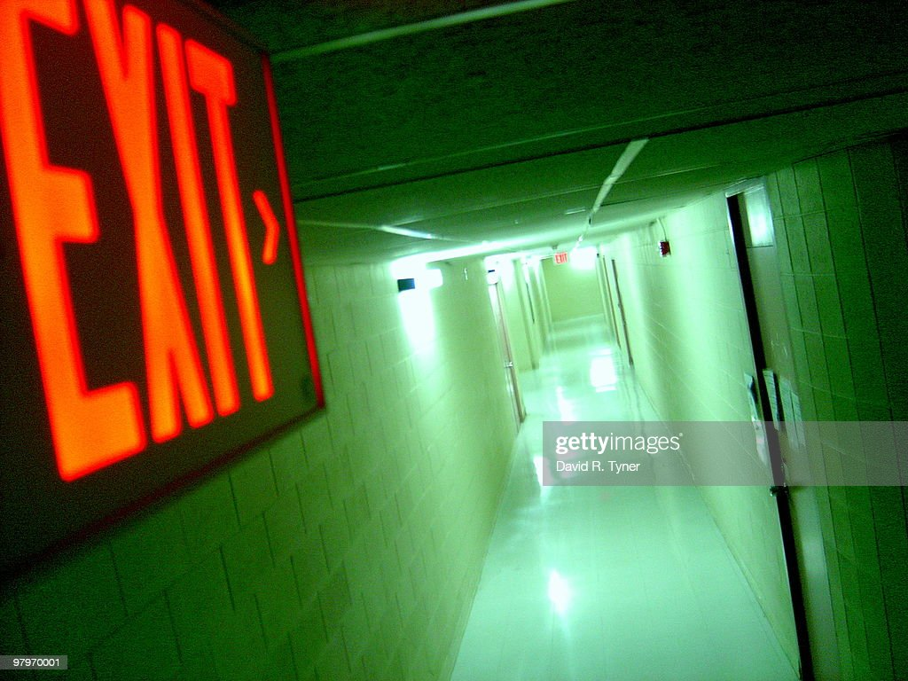 A long hallway with exit sign : Stock Photo