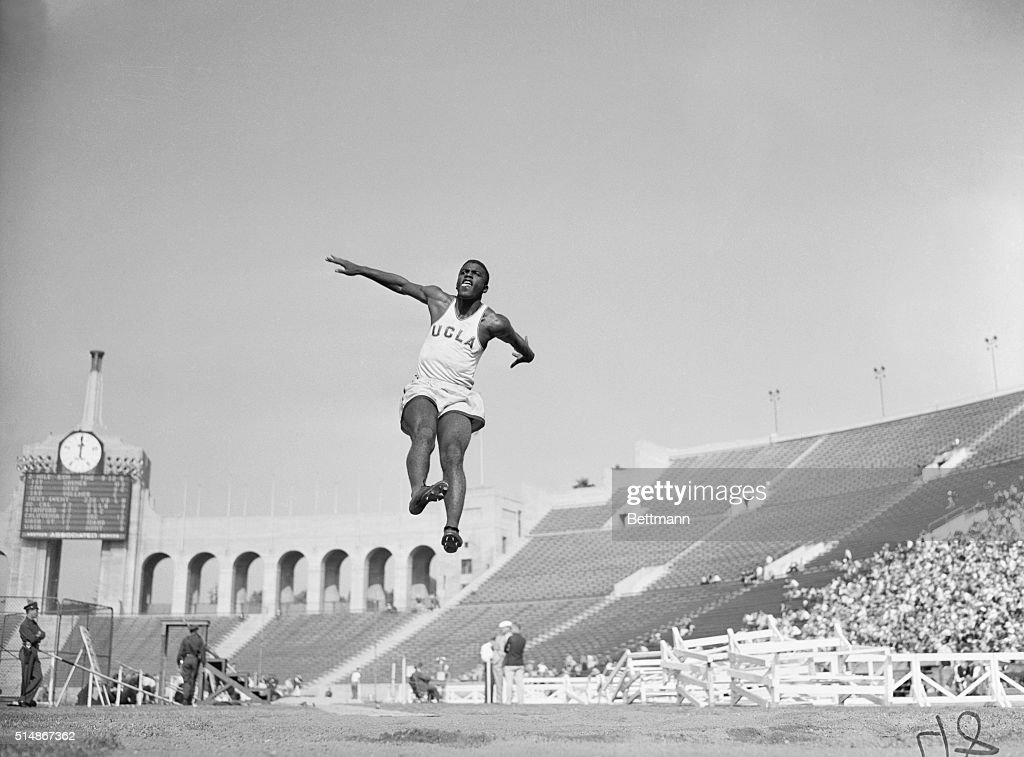 Long jumper Jackie Robinson leaps through the air at a college track meet in the Los Angeles Coliseum 1940