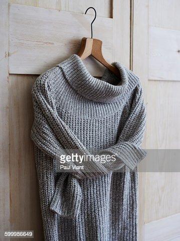 long knitted jumper on wooden coat hanger