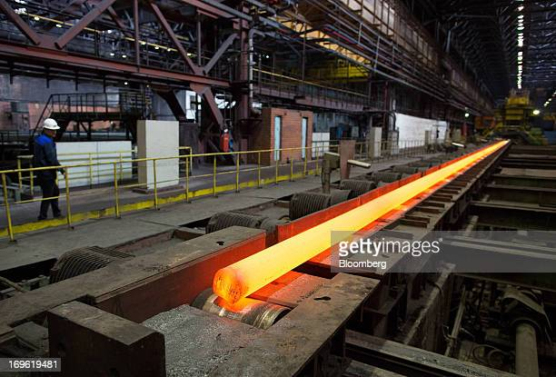 A long length of red hot steel cools in the cooling shop at the Oskol Elektrometallurgical Plant steel mill operated by Metalloinvest Holding Co in...