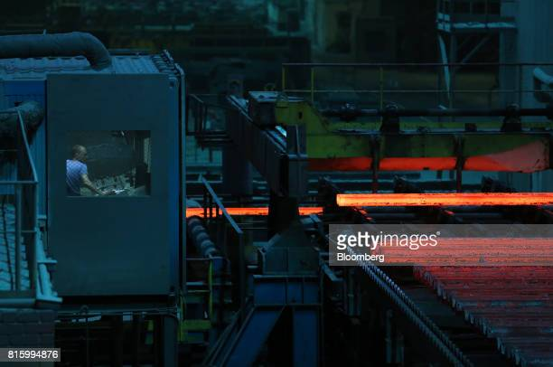 Long lengths of red hot steel move along the production line in the cooling shop at the Oskol Elektrometallurgical Plant steel mill operated by...