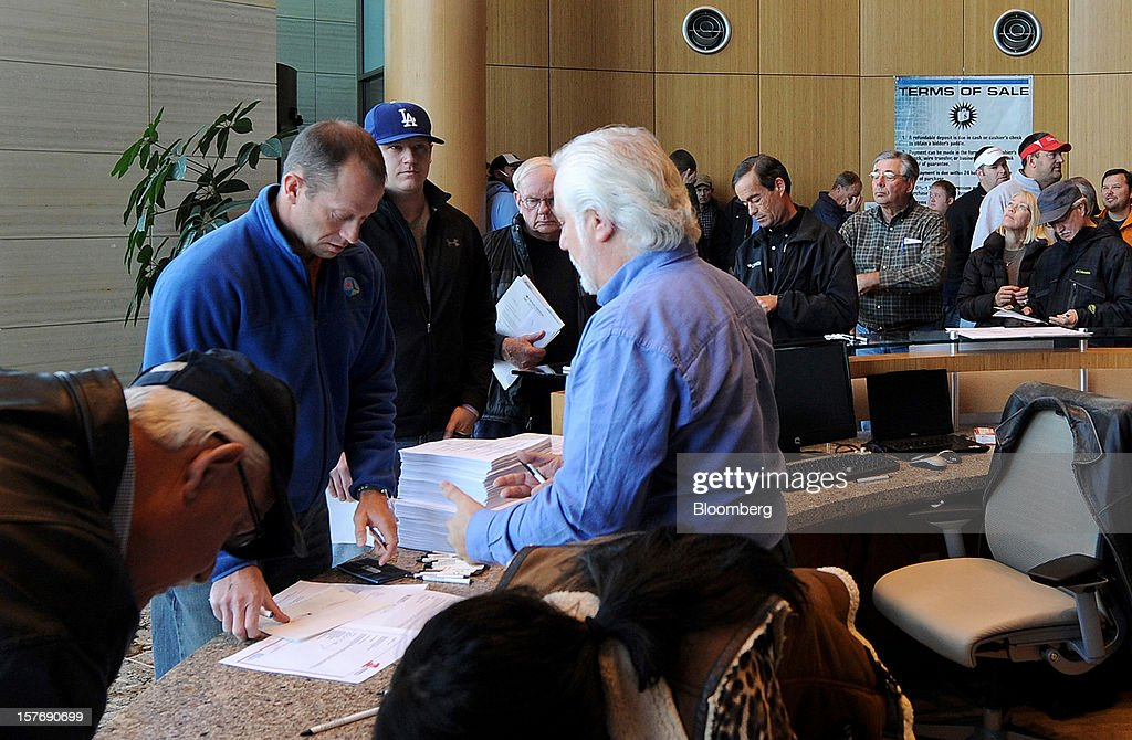 "A long line of bidders register prior to an auction of the contents of the corporate offices of Peregrine Financial Group Inc. and My Verona Restaurant as well as personal items to help with the recovery of assets in the Russell Wasendorf Sr. bankruptcy proceedings in Cedar Falls, Iowa, U.S., on Dec. 5, 2012. Wasendorf, the founder of Peregrine Financial Group Inc., pleaded guilty in September to forging statements from lenders ""to embezzle millions of dollars from customer accounts."" Photographer: Steve Pope/Bloomberg via Getty Images"