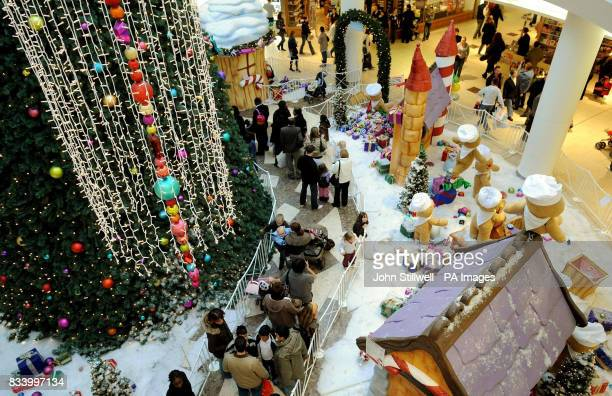 A long line of parents queue with their children to meet Santa Claus at Lakeside shopping centre in Essex where shoppers were out in force with less...