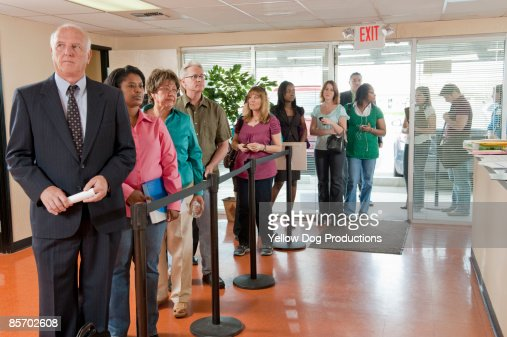 long line of people at unemployment office stock photo