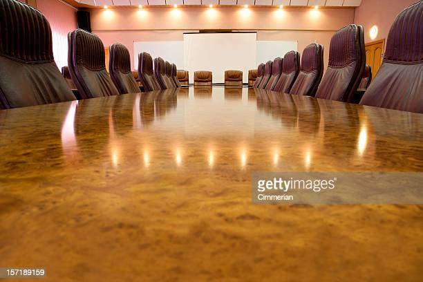 Long marble conference table with leather chairs