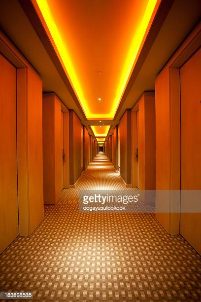 Long, narrow corridor with retro themed carpet and lighting