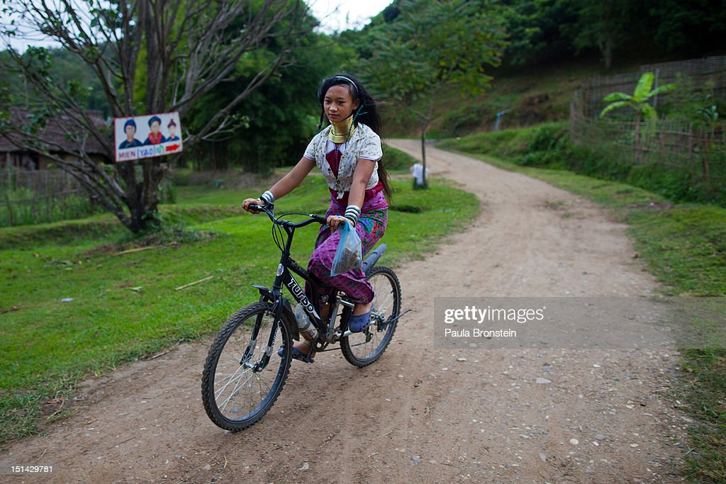 A Long Neck Karen heads out for a bike ride at the end of the day after the tourists have left at the Baan Tong Luang village on September 6, 2012 in Maerim, Thailand. Baan Tong Luang is a fabricated village containing 6 separate Thai Hill Tribes where visitors are expected to pay $16 or 500 Thai bhat for the entrance fee. The ethnic tribes include the Lahu, Hmong, White Karen, Long necked Karen, Yao, Akha. The village opened since 2005 attempts to preserve the old traditions of the ethnic Hill Tribe, also providing an income for them. Life for many of Thailand's Hill Tribe population can be difficult since it can be hard for them to make a living. Their language, costume and culture are different along with the frequent legal problems over Thai citizenship. Hill tribe is a term used in Thailand for all of the various tribal peoples who migrated from Tibet, or elsewhere in China over the past few centuries..