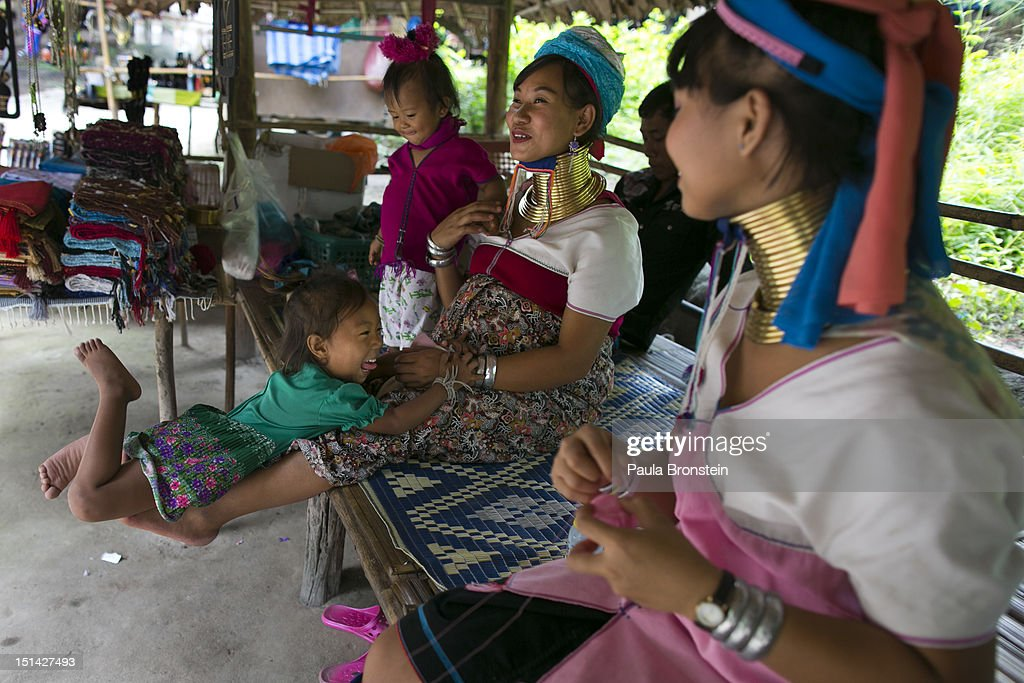 Long Neck Karen mothers chat with each other during a slow day at the Baan Tong Luang hill tribe village on September 6, 2012 in Maerim, Thailand. Baan Tong Luang is a fabricated village containing 6 separate Thai Hill Tribes where visitors are expected to pay $16 or 500 Thai bhat for the entrance fee. The ethnic tribes include the Lahu, Hmong, White Karen, Long necked Karen, Yao, Akha. The village opened since 2005 attempts to preserve the old traditions of the ethnic Hill Tribe, also providing an income for them. Life for many of Thailand's Hill Tribe population can be difficult since it can be hard for them to make a living. Their language, costume and culture are different along with the frequent legal problems over Thai citizenship. Hill tribe is a term used in Thailand for all of the various tribal peoples who migrated from Tibet, or elsewhere in China over the past few centuries.