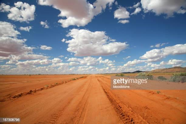 Long orange outback road under a blue sky
